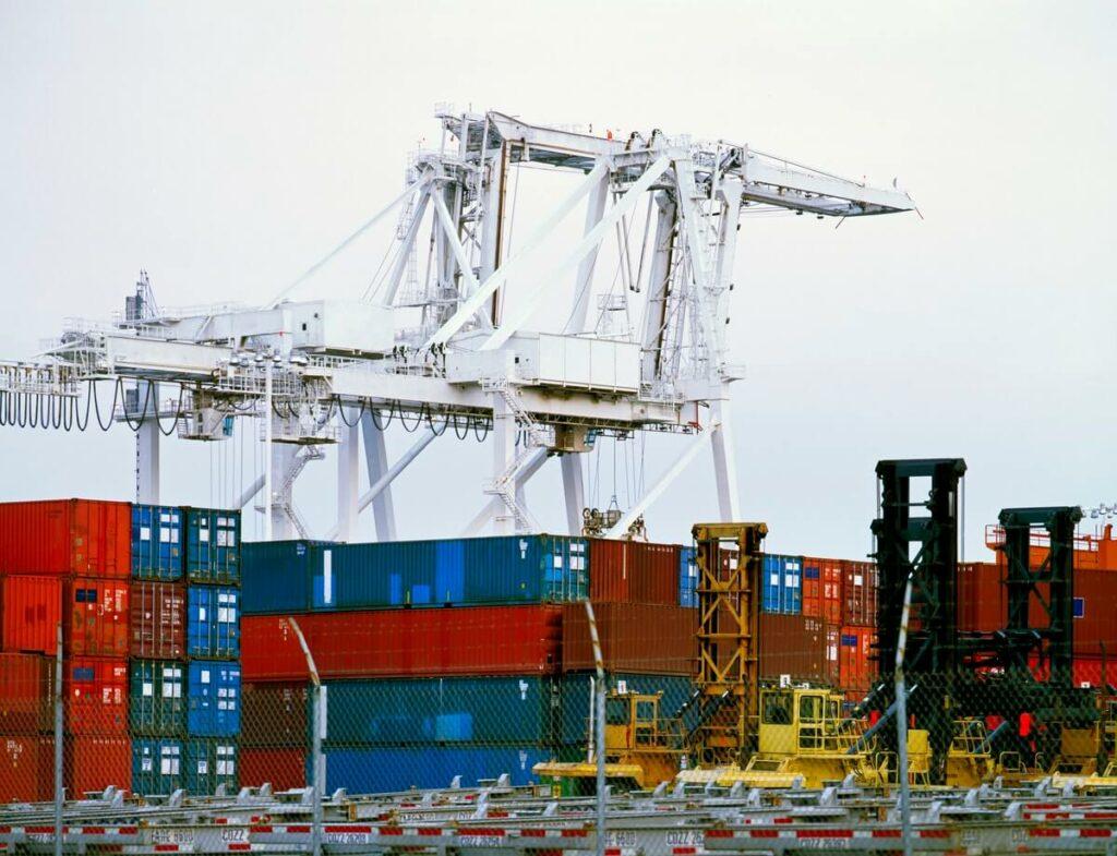 foto mostra um porto com guindastes e contêineres de metal. A finalidade é ilustrar o dropshipping como um dos negócios em alta para 2020