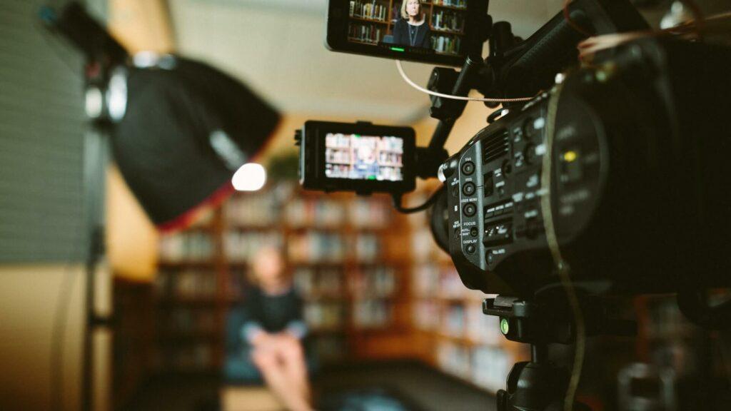 câmera de vídeo vista por trás enquanto grava uma cena que aparece desfocada