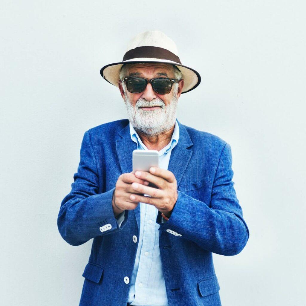 homem de cabelo e barba brancos usando chapéu e óculos e mexendo no celular