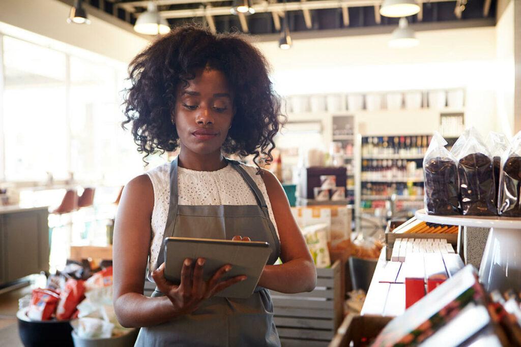 mulher negra de cabelos na altura dos ombros está fazendo a gestão de estoque de um mercado em um tablet