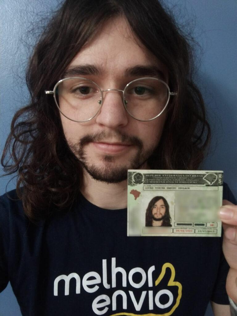 """Homem branco de óculos e cabelos compridos tirando uma selfie enquanto segura uma carteira de motorista. Ele usa uma camiseta em que está escrito """"Melhor Envio"""""""