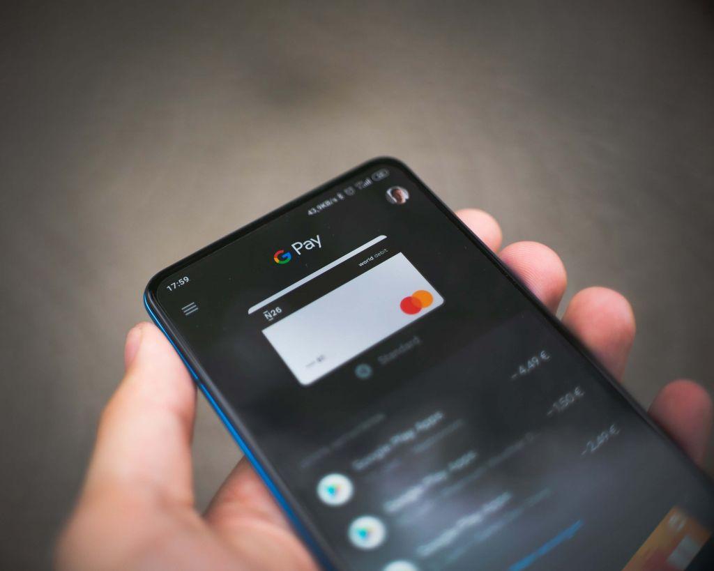 Uma mão segura um celular e na tela aparece o aplicativo de um meio de pagamento digital, o Google Pay.