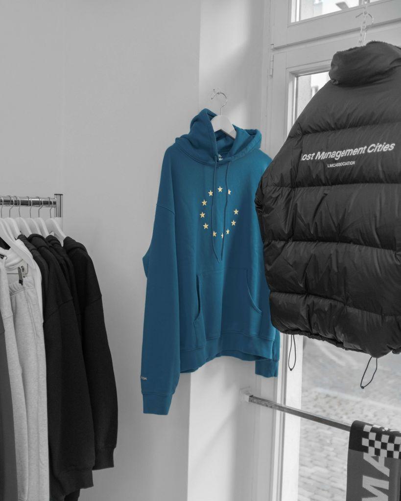 Casacos esportivos e moletons organizados em cabides para a venda de roupas online.