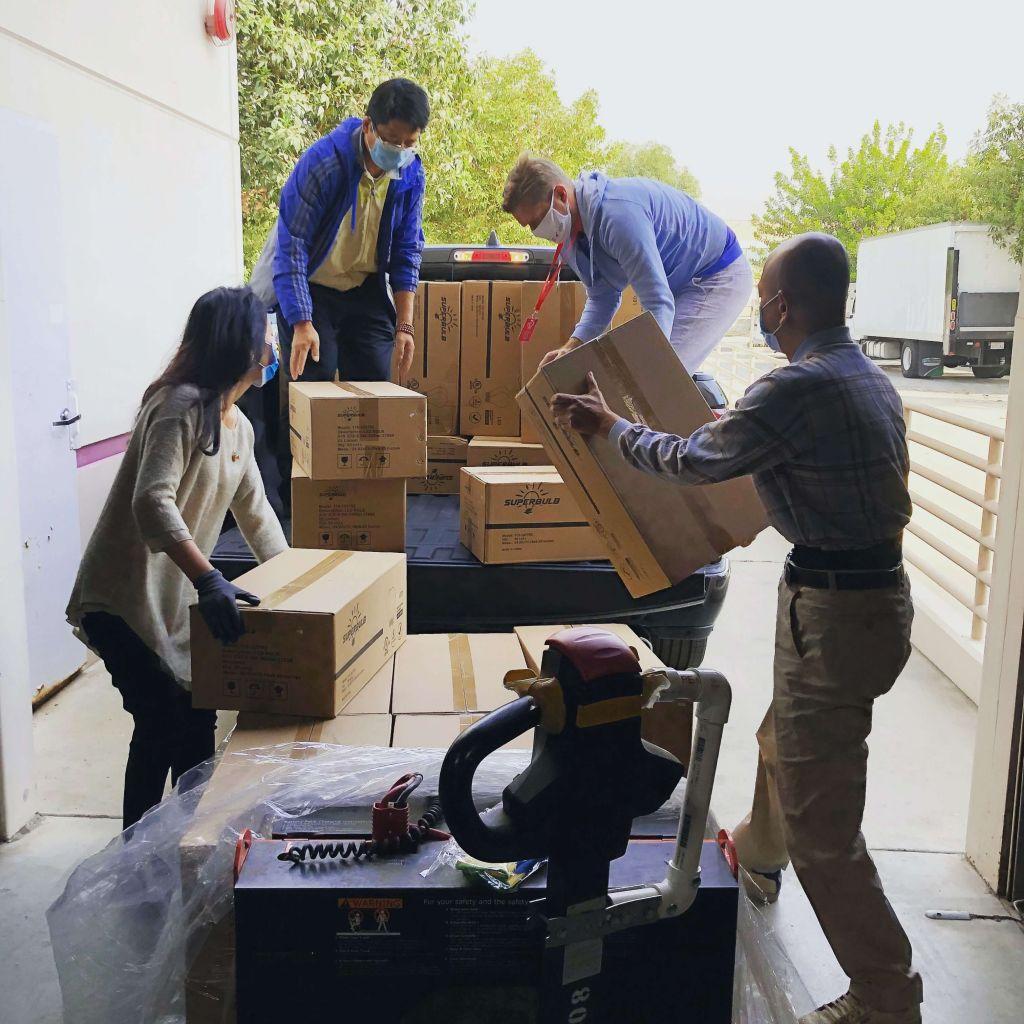 Um grupo de pessoas usando máscara de proteção individual, 3 homes e 1 mulher, organizam caixas na caçamba de uma caminhonete.