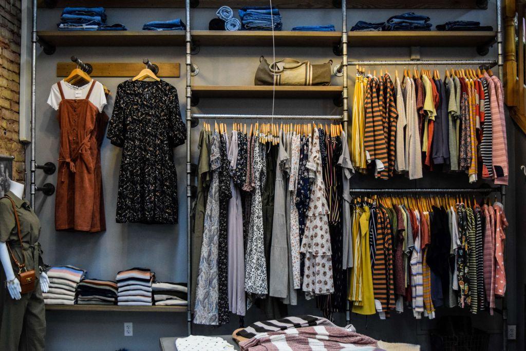 Araras e prateleiras com peças para venda de roupas online.
