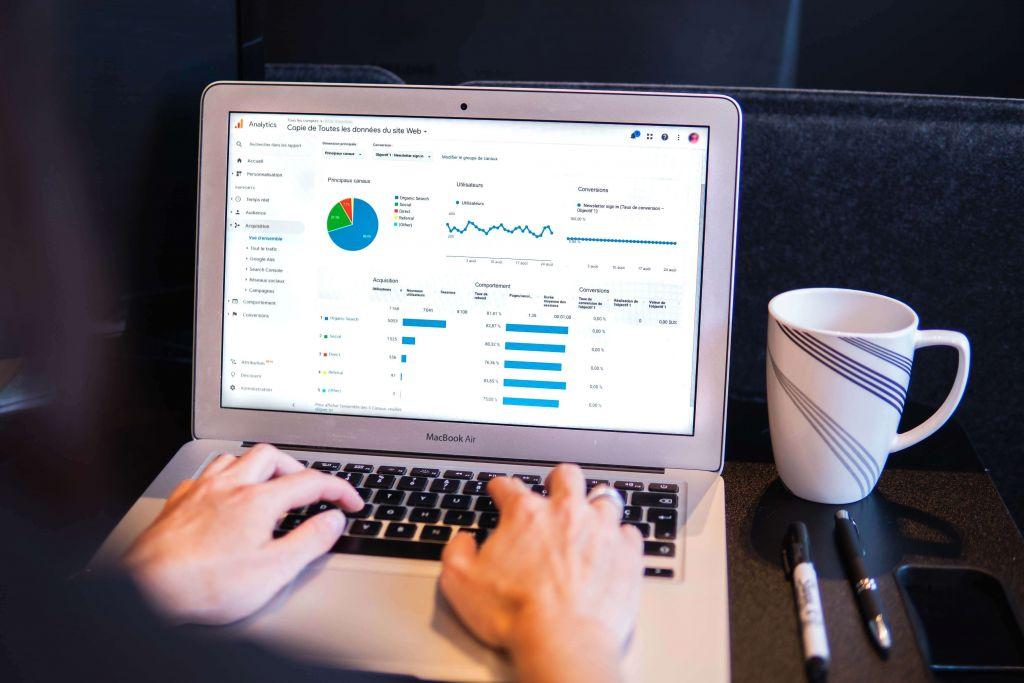 Notebook com gráficos de métricas para e-commerce sendo mostrados na tela.