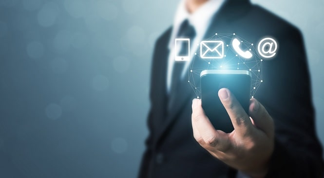 foto de um homem segurando um smartphone, que está rodeado por símbolos de e-mail, telefone e arroba ilustrando atendimento digital