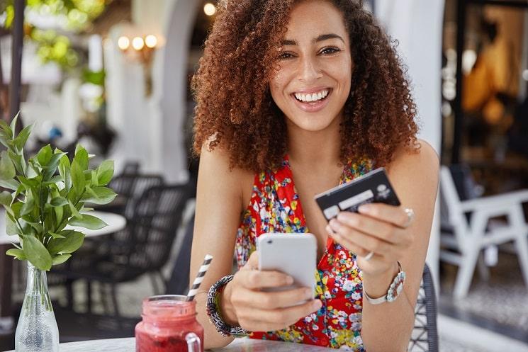 foto de mulher sorrindo segurando um smartphone e um cartão de crédito ilustrando consumidor satisfeito