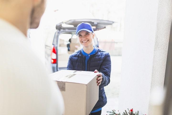 imagem de uma entregadora com uma pacote nas mãos para ilustrar a entrega na devolução de produtos no e-commerce