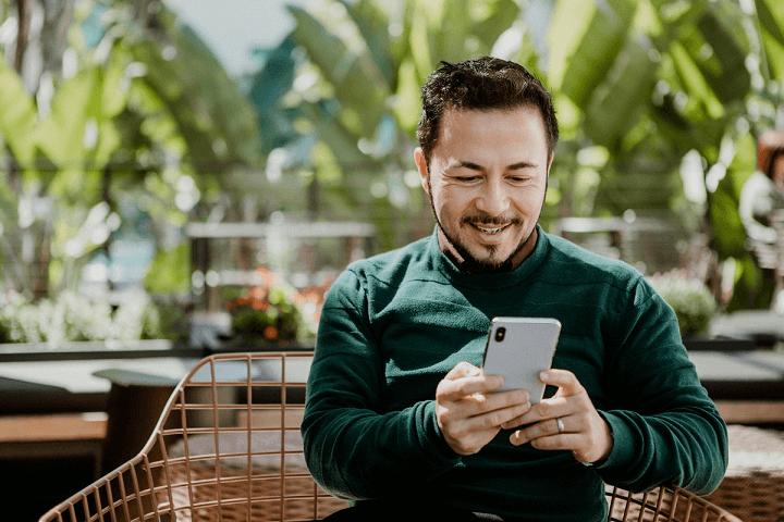 dia do frete grátis imagem de homem olhando sorrindo para o smartphone