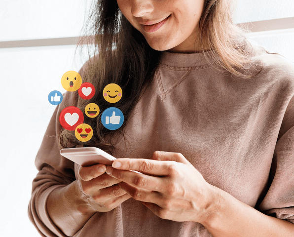 imagem mostra um smartphone nas mãos de uma mulher, rodeado por emojis