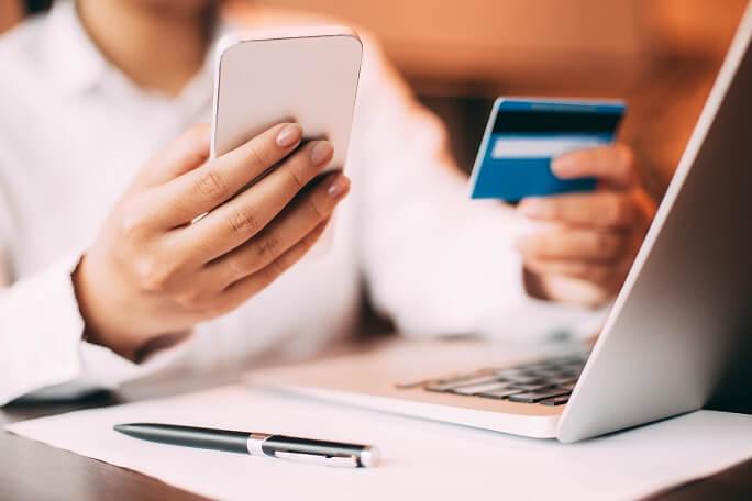 imagem mostra um notebook e as mãos de uma pessoa segurando um celular e um cartão de crédito