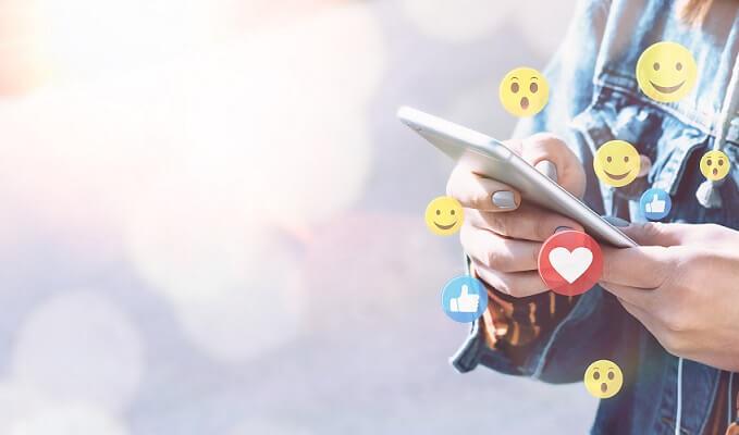 live shopping - imagem mostra as mãos de uma pessoa segurando um smartphone com ilustrações de emojis ao redor