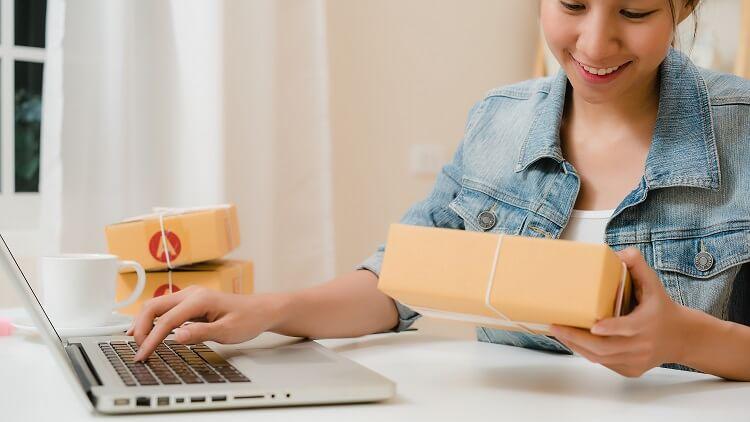 melhor envio como funciona imagem de mulher com uma caixa na mão e trabalhando no notebook