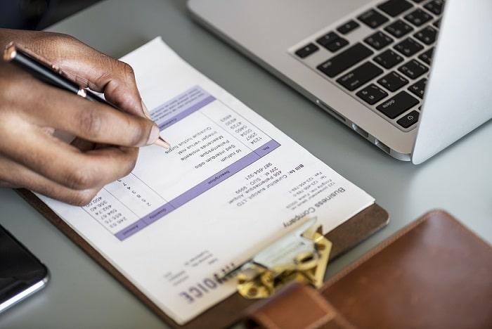 foto de um notebook e um documento fiscal para ilustrar a nota fiscal no e-commerce