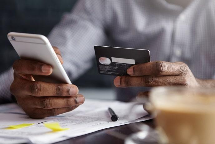 foto das mãos de um homem segurando um smartphone e um cartão de crédito para ilustrar as compras pela internet