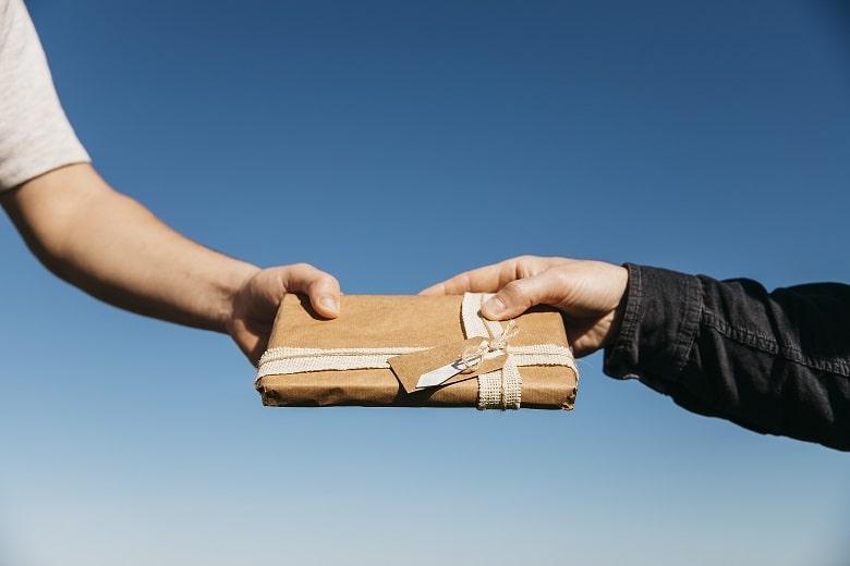devolução de produtos imagem mostra as mãos de duas pessoas segurando um presente