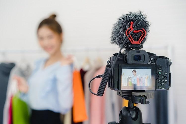 imagem de uma câmera filmando uma mulher mostrando roupas