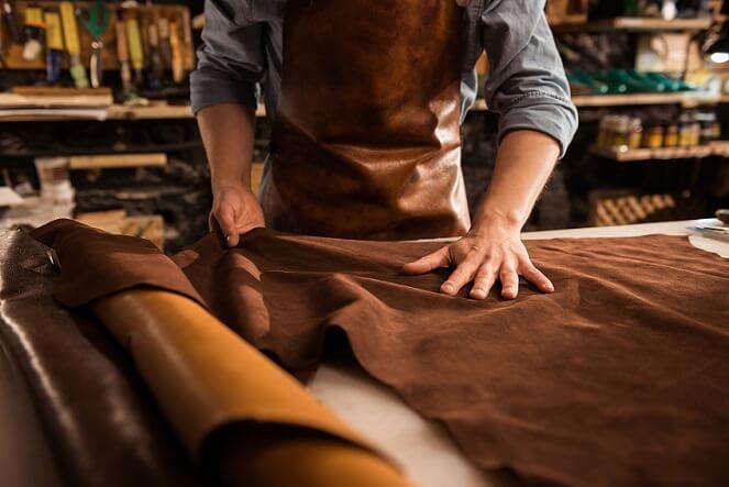 foto de produção de artesanato, com um homem trabalhando com tecidos e materiais em couro em um ateliê