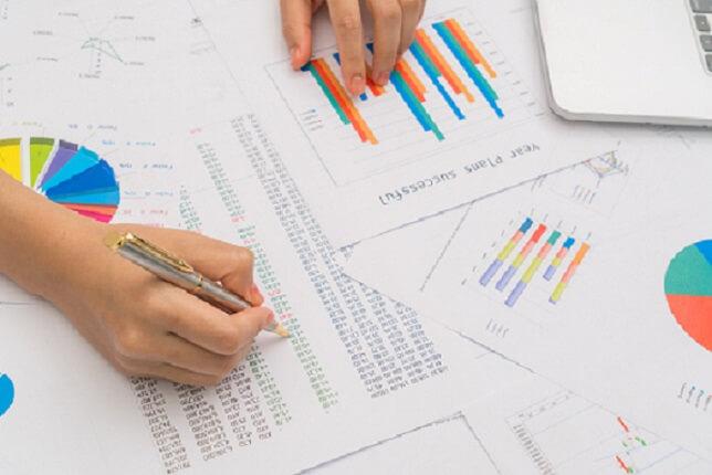 foto mostra a mão de uma mulher fazendo anotações em gráficos e planilhas