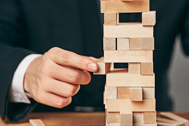 abrir uma loja virtual imagem mostra mão de homem empilhando pequenos blocos de madeira