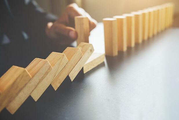 foto de bloquinhos de madeira alinhados simulando efeito dominó