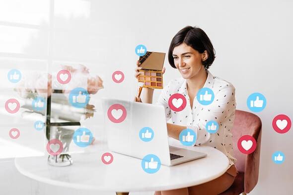 mulher olha para um notebook, cercada de ícones de curti e amei em redes sociais