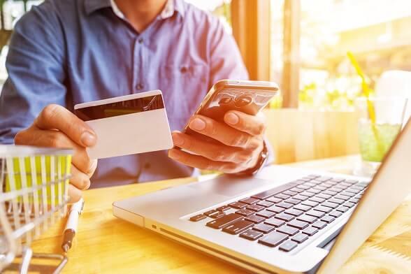 foto de um homem com cartão de crédito na mão e em frente a um notebook