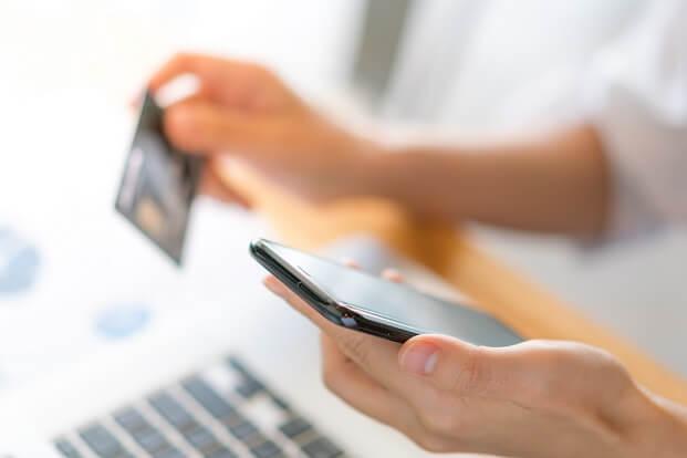 mãos femininas seguram um smartphone e um cartão de crédito em frente a um notebook, dando a ideia de compras em loja virtual