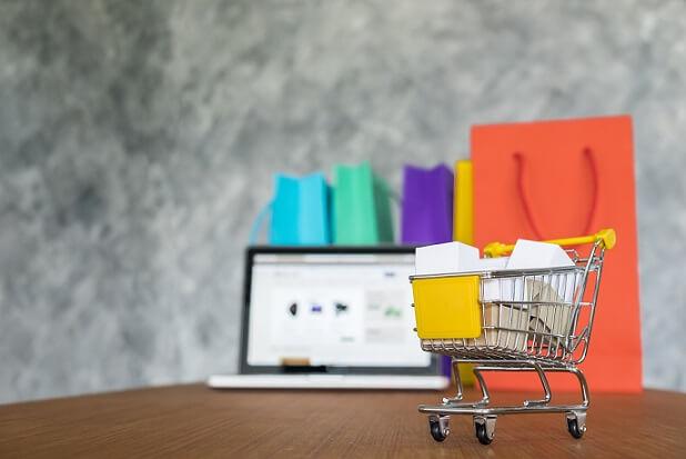 imagem de um notebook ao fundo, cerca por carrinho de compras e sacolas, simulando uma loja virtual
