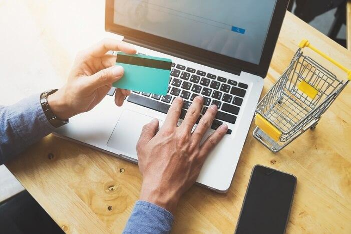 como vender online foto das mãos de um homem segurando um cartão de crédito e trabalhando em um notebook
