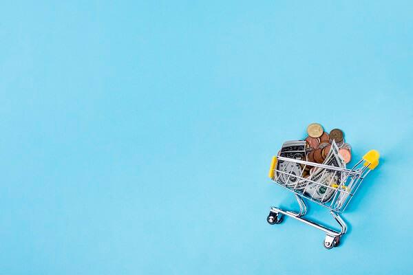 como vender online marketplaces imagem de um carrinho de compras com dinheiro dentro, em frente a um fundo azul