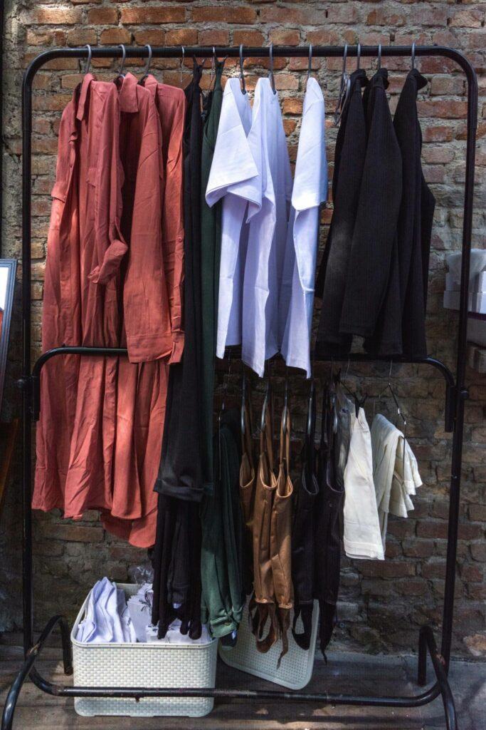 foto de uma arara com roupas penduradas no estoque loja virtual